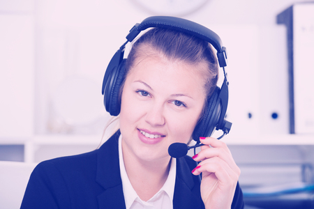Portrait of young woman in black suit which is talking by headset with client in the office. Foto de archivo