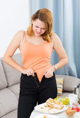 Portrait of young female trying zip up pants near the table with pie Stock Photo