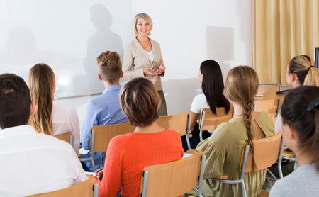 Gruppe von Studenten, die aufmerksam dem Vortrag der Lehrerin im Klassenzimmer zuhören