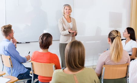 Mature female speaker giving presentation for students in lecture hall