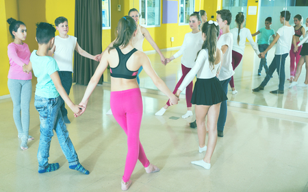 Group of tweens exercising folk dance, forming circle with female teacher in choreography class Stock Photo