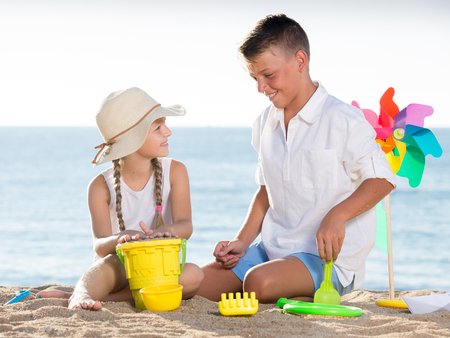 happy two kids in elementary school playing with toys on beach on summer day