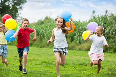 cheerful smiling elementary school age boy and girls holding air balloons and running in summer park. Selective focus Stock Photo