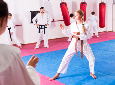 Preteen active girl practicing taekwondo movements with male trainer supervision