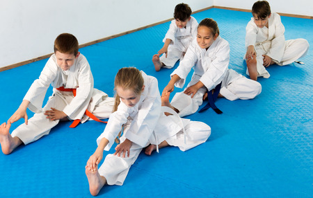 Cheerful children getting ready and stretching for karate class