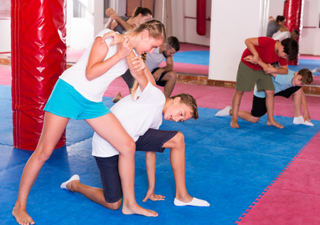 Kids with adults practicing effective techniques of self-defence in training room Stockfoto