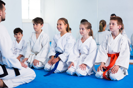 Young smiling man training new karate moves with kids during class. Focus on boy