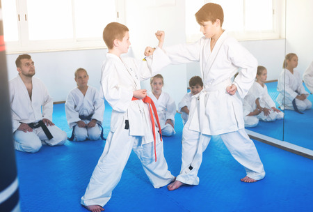 Pair of children trying in sparring to use new moves at karate class