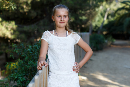 Portrait of smiling teen girl standing near fence  in summer green park Stock Photo