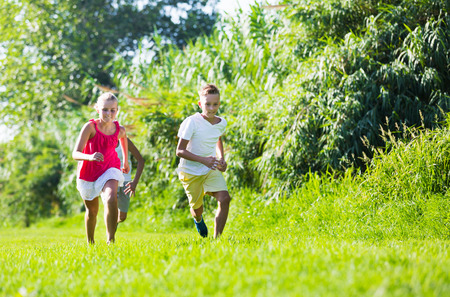 Happy kids playing active games in summer park chasing each other Stock Photo