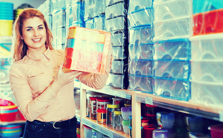 Smiling female saleswoman showing plastic containers for storage in household shop Stockfoto