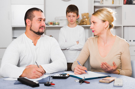 Serious young family working with papers at home on background with waiting son