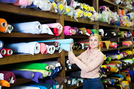 happy young blonde woman choosing textiles for dressmaking in fabric shop 版權商用圖片