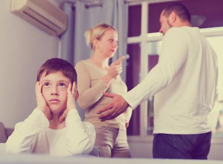 Sad desperate little boy during parents quarrel in home interior 免版税图像