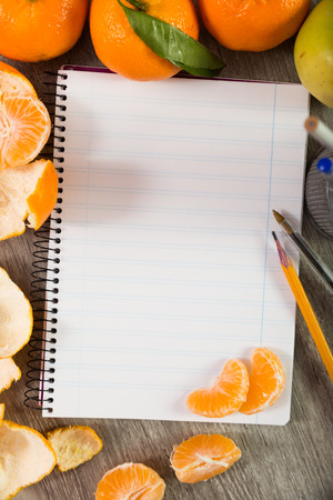 Notebook with writing utensils surrounded by fruit