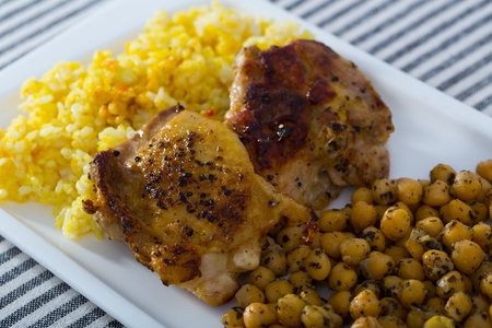 Appetizing fried chicken thighs with stewed chickpeas and spicy rice on white platter