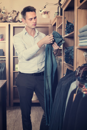 Young man is choosing on new pants in men's clothes store.