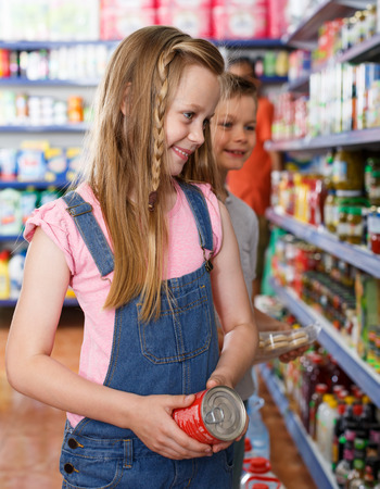 Smiling kids choosing preserved meal for home in the supermarket