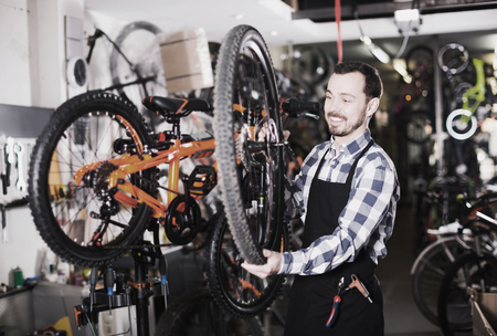 Worker in apron shows structure of bicycle wheel in sporting goods shop