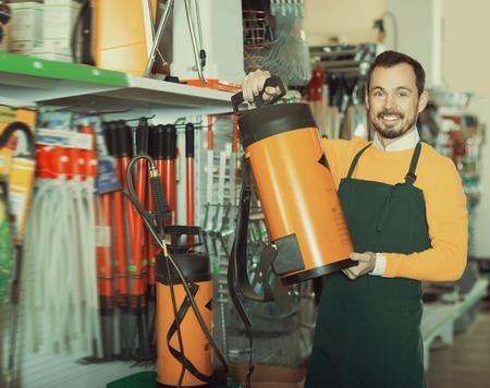 Glad guy deciding on best garden sprayer in garden equipment shop