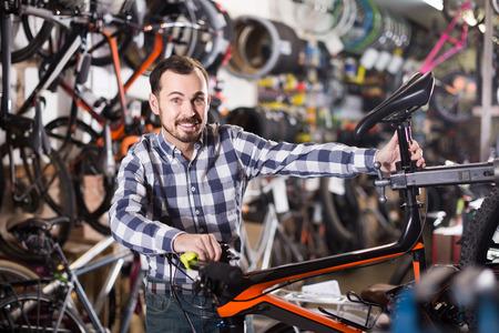 Smiling man checks bicycle handlebar in shop when choosing bike