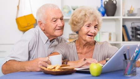 Happy elderly pair using laptop sitting at table at home