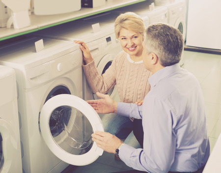 Mature married couple in shop of household appliances are choosing home modern washing machine Stockfoto