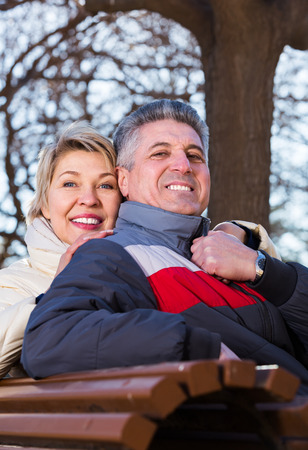 Positive husband and wife hugging each other sitting on park bench