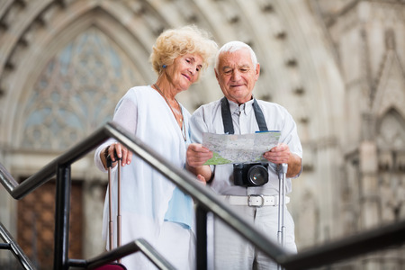 Senior happy belgian  woman and man traveling together looking for destination with city map