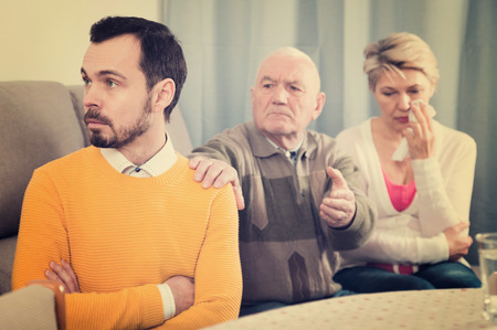 Elderly grandfather teaches and instructs grandson and at home in presence of his mother