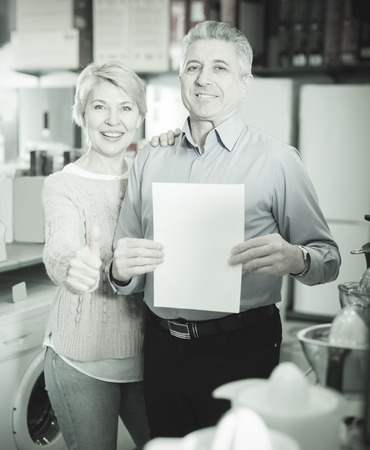 Mature couple took credit for home appliances in center of household appliances 스톡 콘텐츠
