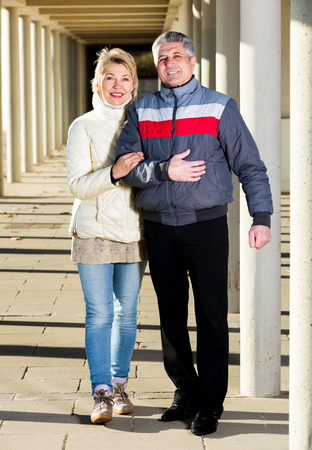 Positive married couple goes for walk between concrete pillars on sunny day