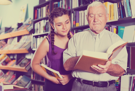 grandfather with girl are reading books in bookstore. Stockfoto