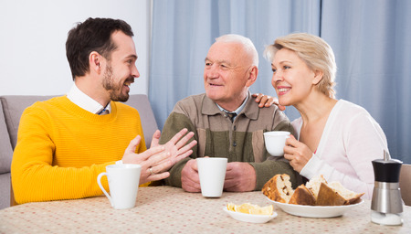 Elderly grandfather, mother and son drinking coffee and talking at table at home