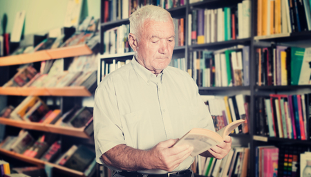 Old person is choosing book for reading in free time in bookstore.