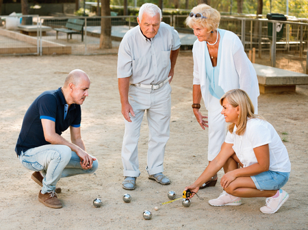 Satisfied pleasant smiling family playing petanque in outdoor Stockfoto