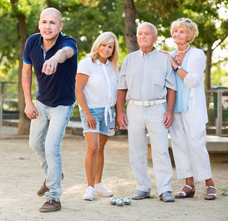 Glad cheerful  family playing petanque in outdoor Stock Photo
