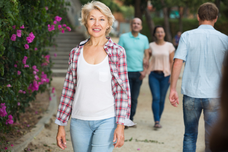 Portrait of cheerful mature woman walking in the park at leisure 免版税图像