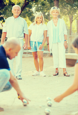 Positive mature people friends playing petanque together in park outdoor