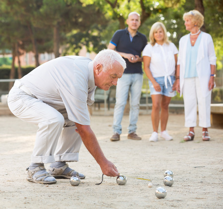 Positive aged people playing bocce in the garden