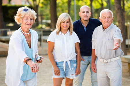 Positive smiling family playing petanque in outdoor