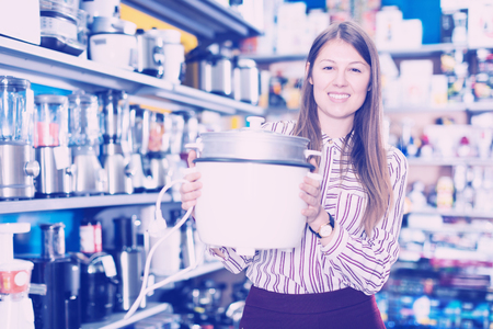 Young saleswoman offering slow cooker in household appliances shop