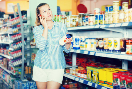 Female with phone choosing mayonnaise at the modern supermarket Stock Photo