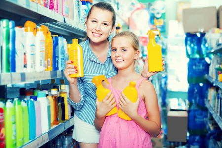 happy mother with girl choosing bottles of sun protection for purchase indoors Archivio Fotografico