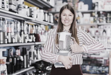 Smiling girl seller showing liquidiser in domestic appliances section Stock fotó