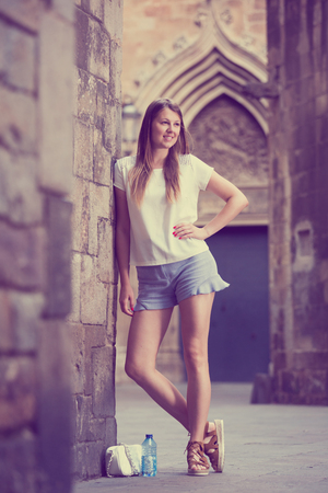 Happy young woman strolling around city standing near old stone wall