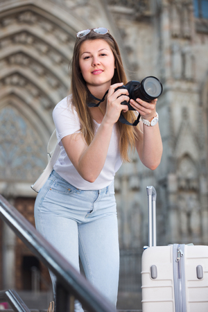 Woman tourist is taking photos on her camera while journey through the city. Stock Photo