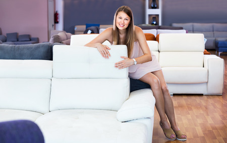 Adult happy  positive  female touching sofa in the furniture store before the buying