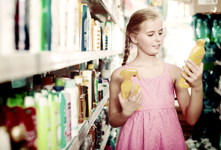 Young customer holding spray and lotion of sun protection at the shop Stock Photo