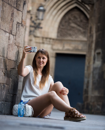 Happy young woman taking selfie while sitting near old stone cathedral wall